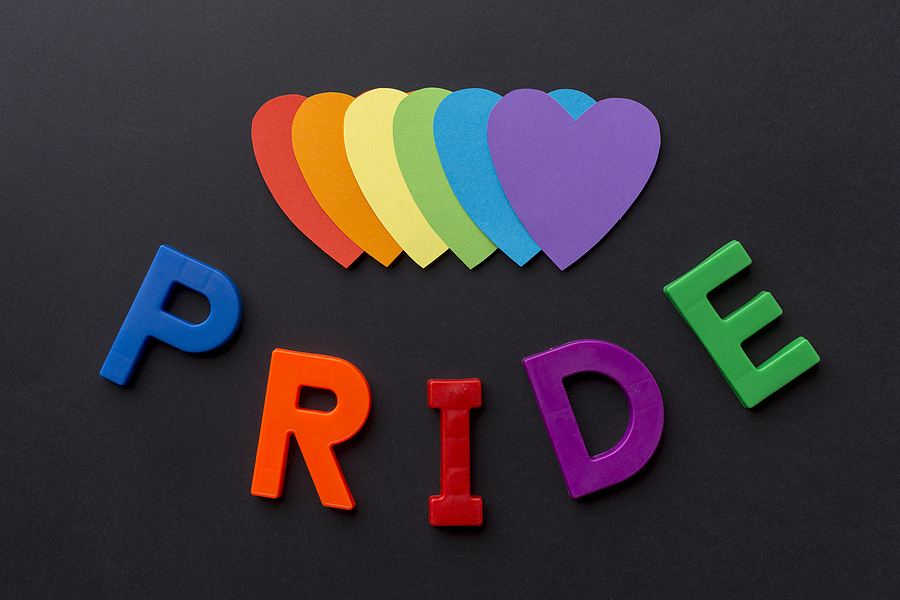 """black background with rainbow colored hearts with words """"Pride"""" in multiple colors below"""